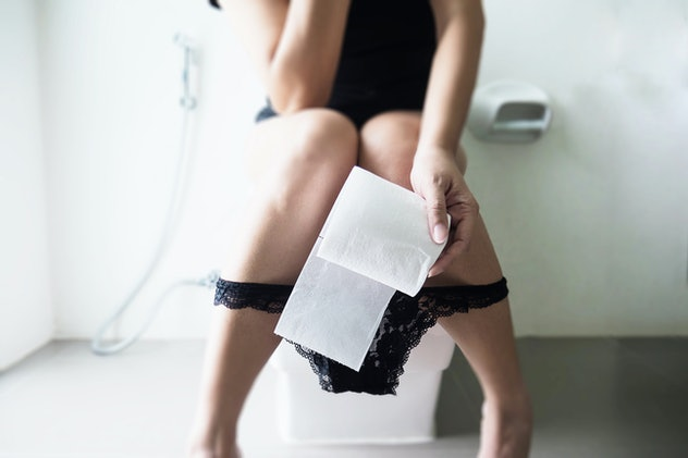 Woman sitting on toilet bowl holding tissue paper