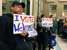 Residents in support of continued refugee resettlement hold signs at a meeting in Bismarck, N.D., Mo...