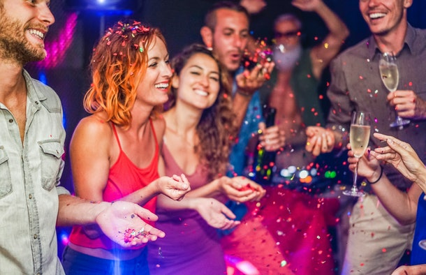 Happy friends making party throwing confetti, dancing and drinking champagne with dj mixing music - Entertainment, fun, new year's eve, nightlife, concept - Focus on blond man hand