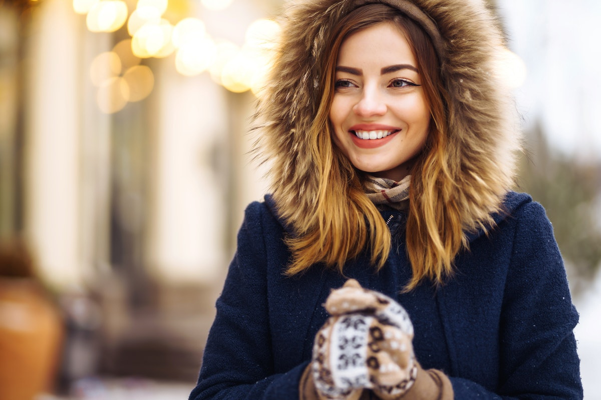 Beautiful  girl in a blue jacket and knitted hat and mittens posing in street of city. Garland ligh...