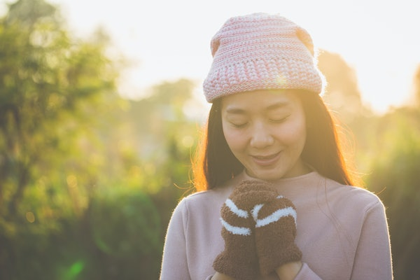 Winter and spring, Beautiful woman wearing knit sweater and gloves and earmuff, holding hands for warmth in the morning in winter.