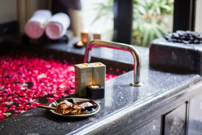 Romantic luxury bathroom idea for couple. Black Marble Bathtub with red rose petals, decorated with candles, bath accessories and towels. Relaxing atmosphere, chic and beautiful design interior in spa