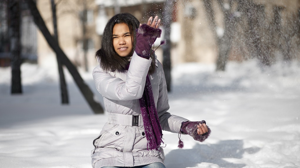 Beautiful smiling american black female sitting in the snow outdoors playing with snow