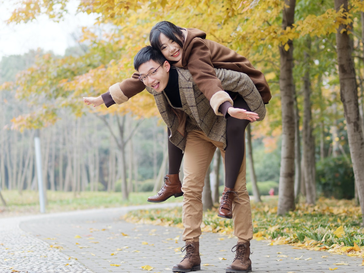 Portrait of smiling young girlfriend piggyback boyfriend during romantic walk in autumn park alley, ...