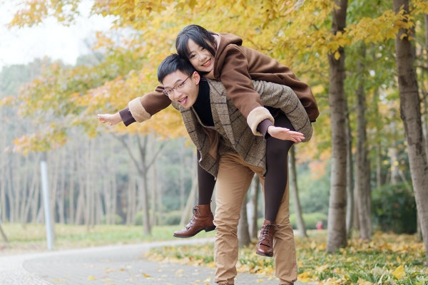 Portrait of smiling young girlfriend piggyback boyfriend during romantic walk in autumn park alley, excited couple looking at camera have fun outdoors, playing foolish, man carry lover on his back.