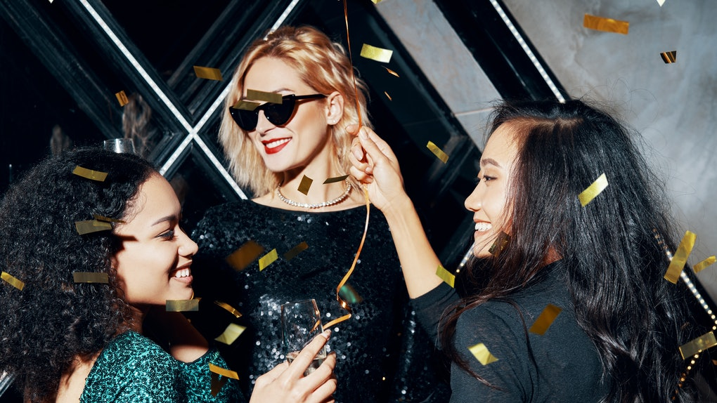 Pretty multiethnic young women have fun together celebrating with confetti on party.  Friendship and event celebration concept