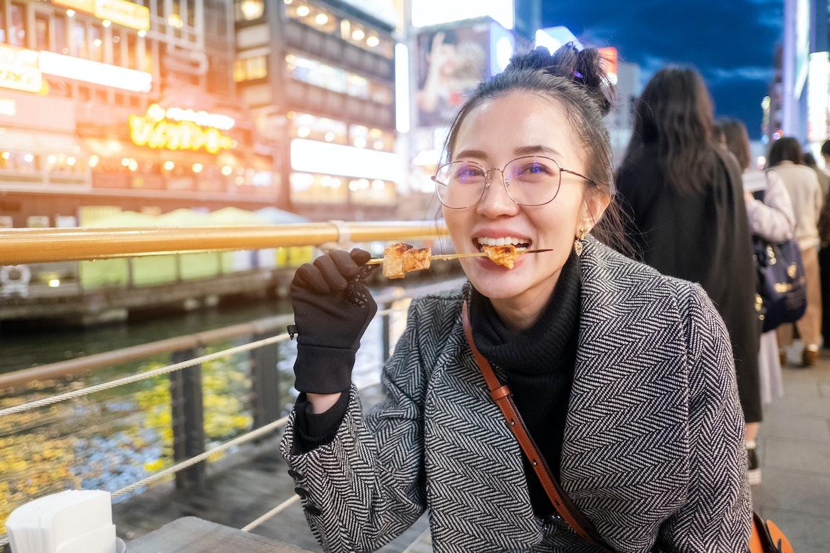 Young woman tourists enjoy eating street food in walking at street shopping center Dotonbori in Osak...