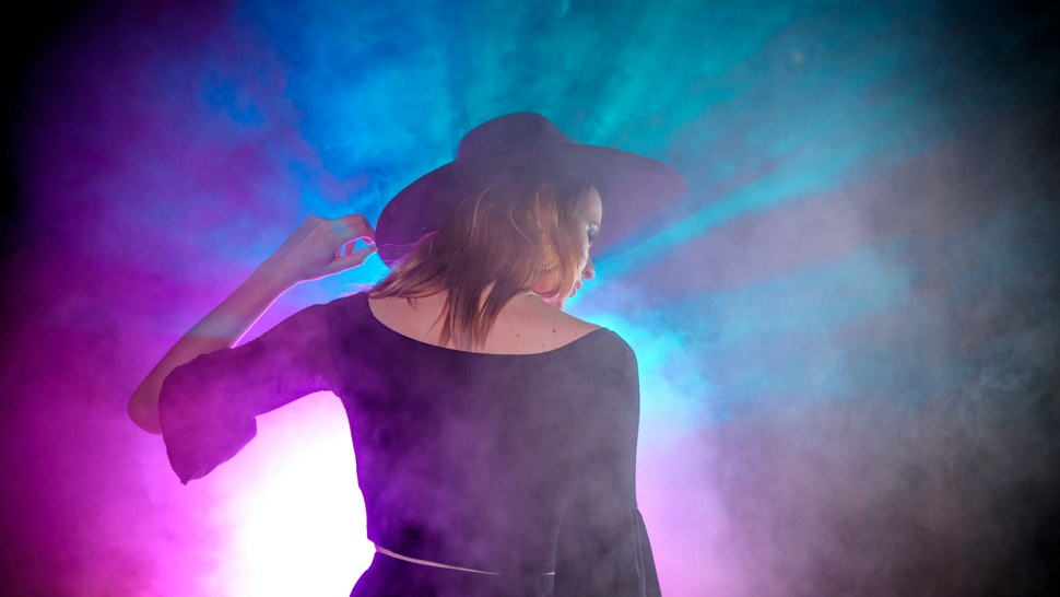 Witch/Wiccan Fashion inspired model with a wide brimmed black hat and black clothing.  Shot with a LED lighting array for high color contrast and with theatrical fog. Model against a black background