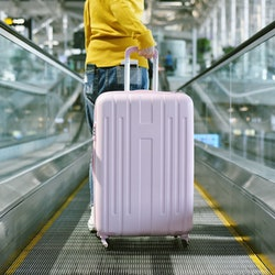 Woman traveler carry big suitcase on escalator walkway at the airport terminal, Passenger walking with luggage to departure check-in counter, Tourist arrive at destination, Travel concept.