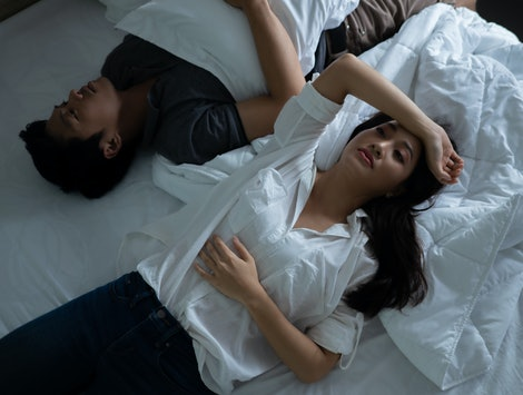 Asian couples are very stressed. they are in bed thinking