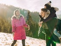 Three friends laugh and have fun outside on a winter vacation for the holidays.