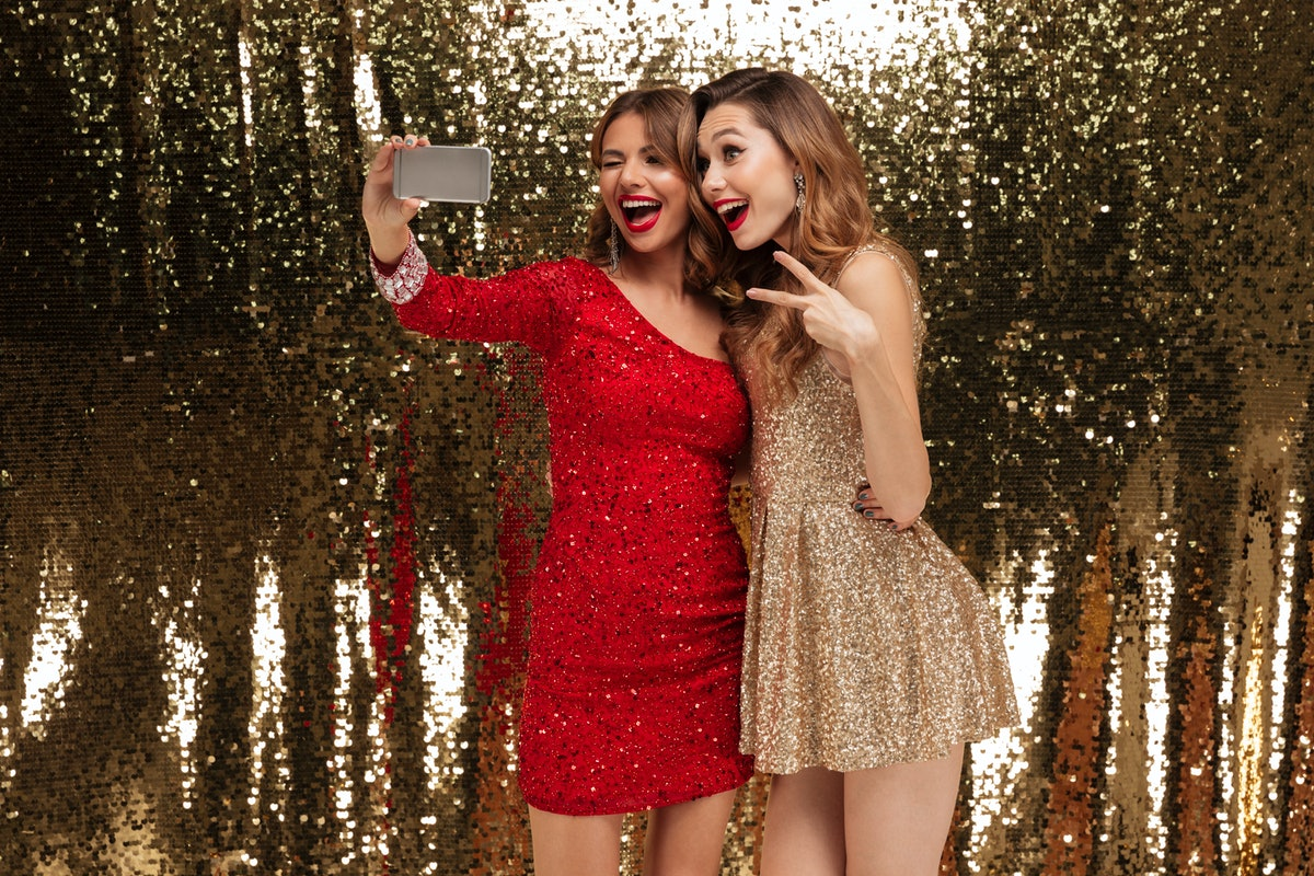 Portrait of two pretty happy women in sparkly dresses taking a selfie while standing together and sh...