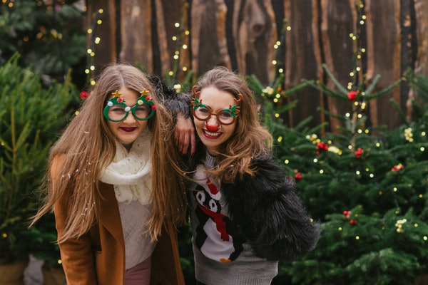 Two girls smile and pose in front of Christmas trees with festive sweaters and glasses on for SantaCon.