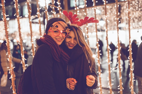 Two girls smile in front of fairy lights outside around Christmastime.