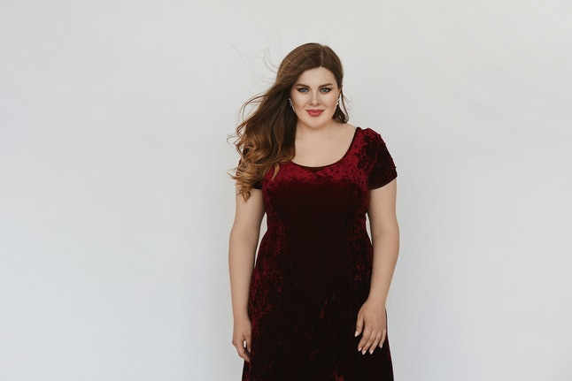 Beautiful plus size model girl in modish red velvet dress isolated at white background. Young fat woman with bright makeup and with stylish hairstyle posing in studio. Concept of XXXL fashion.