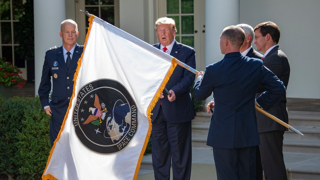 """The flag of the United States Space Command is displayed during the ceremony where United States President Donald Trump established the US Space Command in the Rose Garden of the White House. The Space Command will be the lead military agency for the planning and execution of space operations and will be a step towards establishing a Space Force as a new military service. At left is General John W. """"Jay"""" Raymond, Commander, Air Force Space Command."""