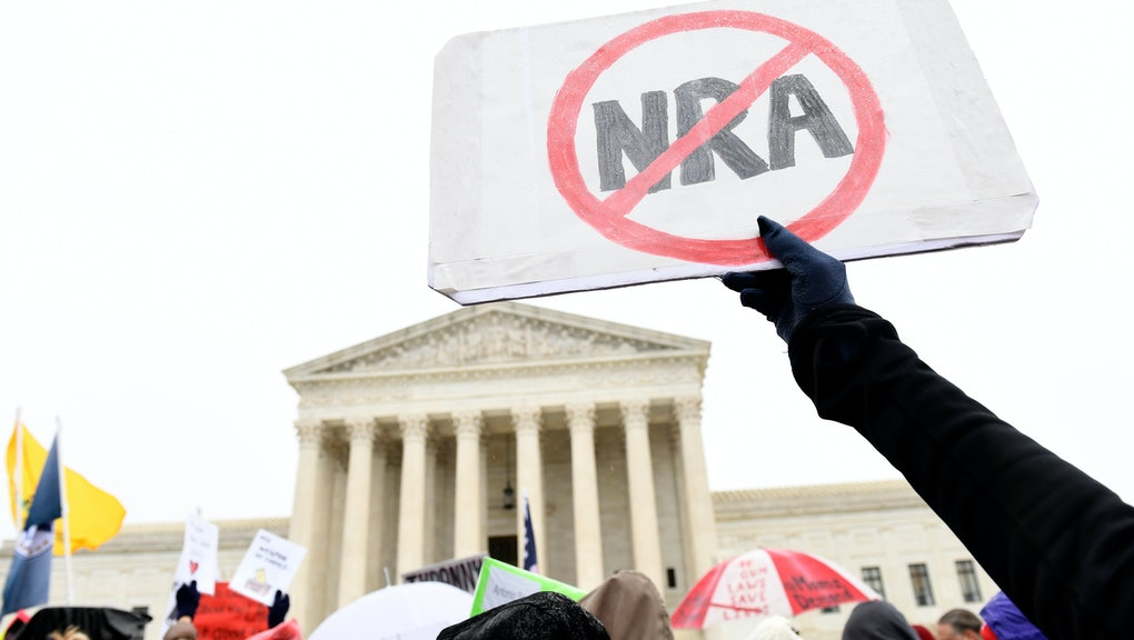 Gun protest, NRA. Protesters gather outside the Supreme Court in Washington, during arguments in the first gun rights case before the Supreme Court in nine years. The case was filed by three New York City gun owners who are challenging a ban on carrying a licensed handgun outside city limits to a gun range, shooting competition or second home outside city limits