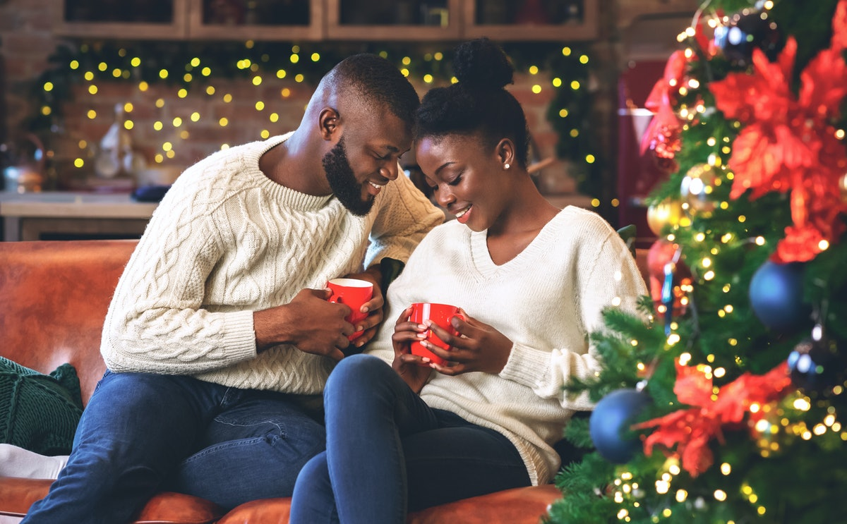Celebrating Christmas together. Young african couple holding red mugs, reading coffee grounds to lea...