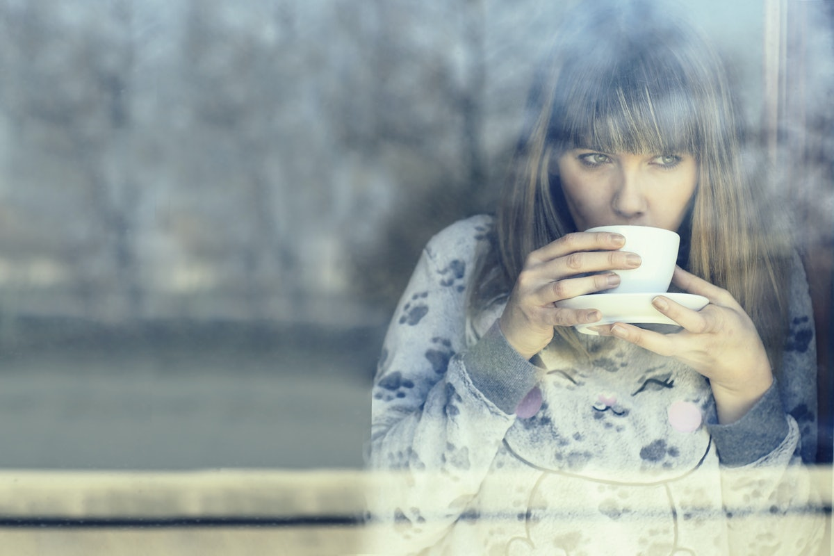young woman in night dress drinking warm coffee or tea  inside home looking out through the window g...