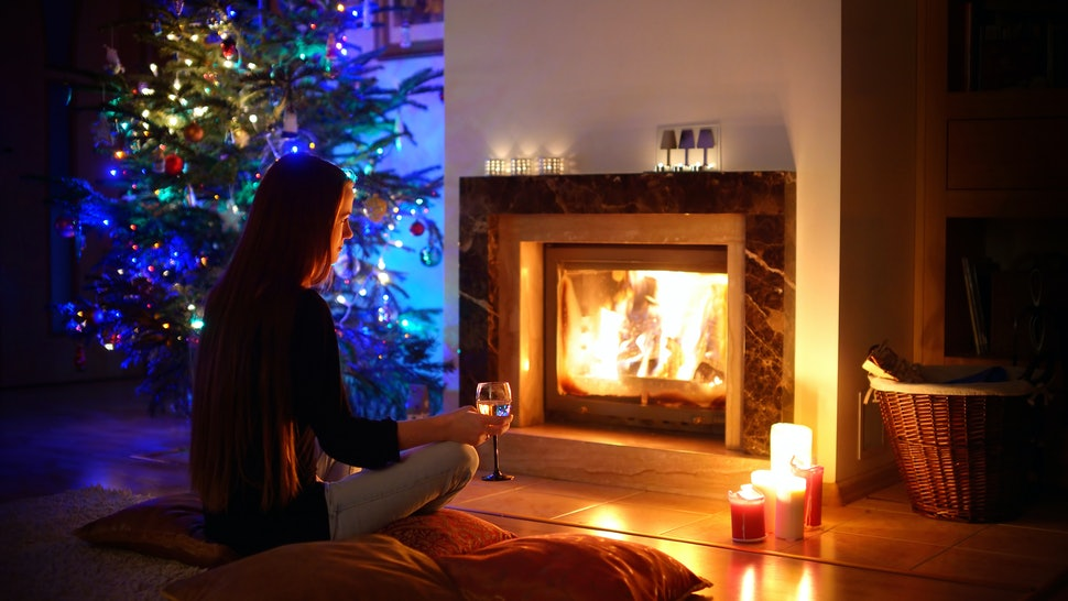 Woman having a drink by a fireplace in a cozy dark living room on Christmas eve
