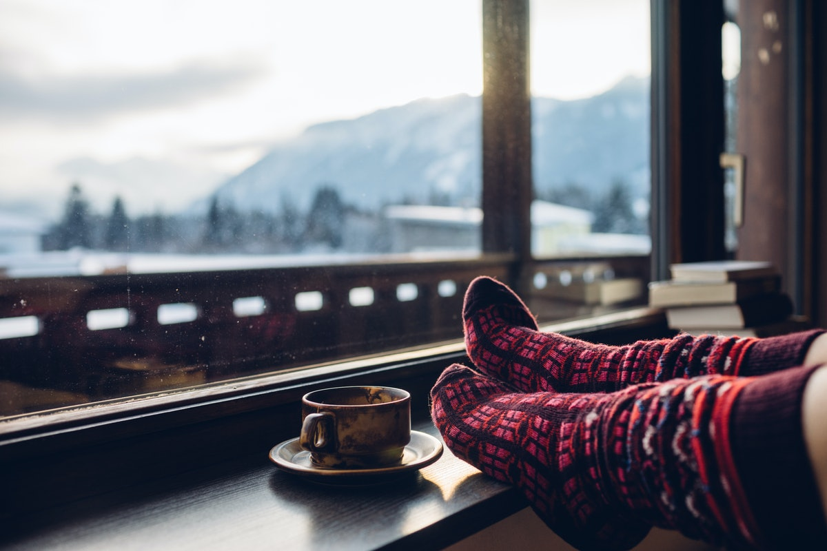 Feet in woollen socks by the Alps mountains view. Woman relaxes by mountain view with a cup of hot d...