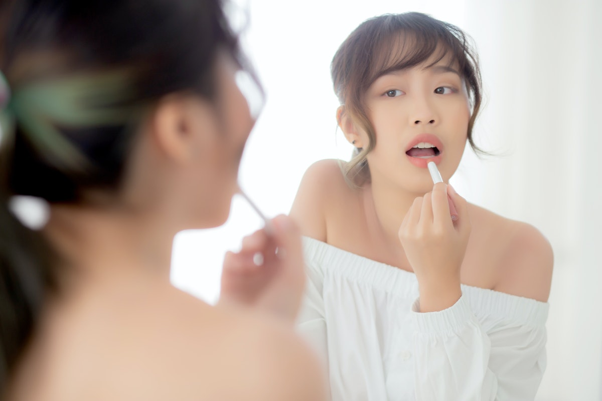 Beautiful portrait young asian woman looking mirror applying makeup lipstick at room, beauty lips asia girl makeup and cosmetic fashion on mouth at home, lifestyle and health care concept.