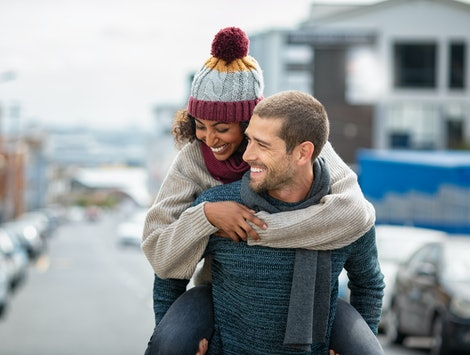Smiling man giving piggyback ride to woman in the city. Young multiethnic couple in cold clothes walking in street and having fun. Cheerful girlfriend with wool cap and boyfriend in sweater in winter.
