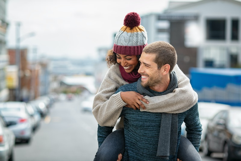 Smiling man giving piggyback ride to woman in the city. Young multiethnic couple in cold clothes wal...