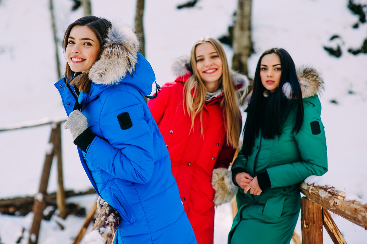 three cheerful young women in winter mountains