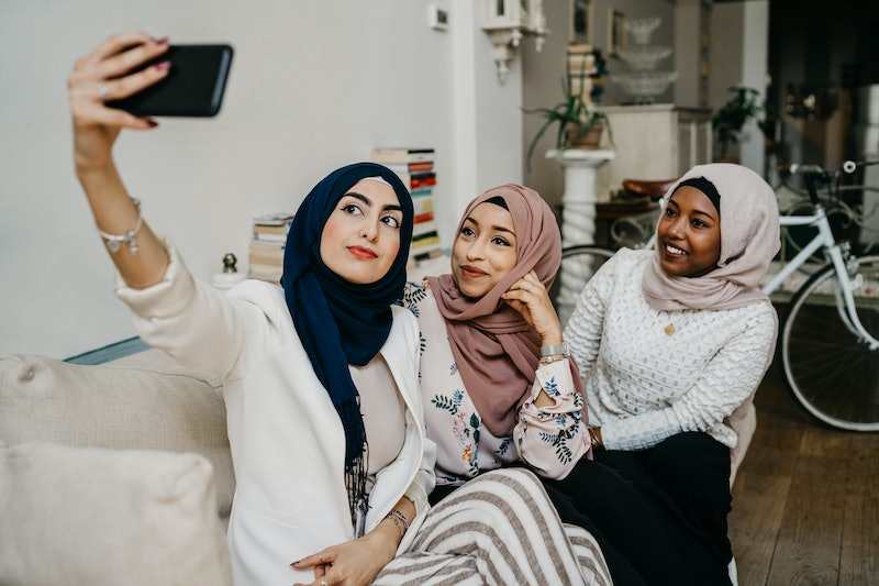 Arab friends taking a selfie on the sofa in house - Millennials in a moment of intimacy and relaxation