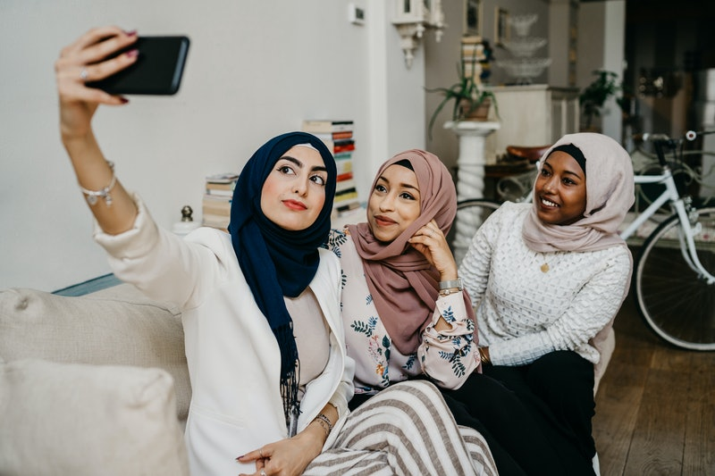 Arab friends taking a selfie on the sofa in house - Millennials in a moment of intimacy and relaxati...