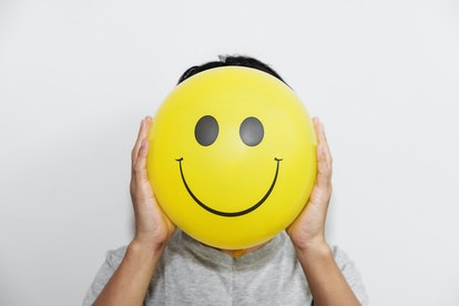 A man holding yellow balloon with smile face emotion instead of head. Positive Thinking concepts. hi...