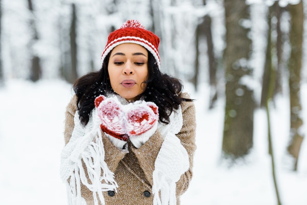 beautiful african american woman blowing snow in winter forest