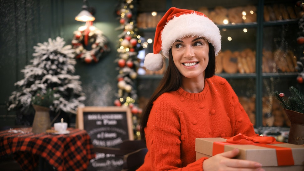 Beautiful woman with gift box in decorated cafe. Christmas celebration