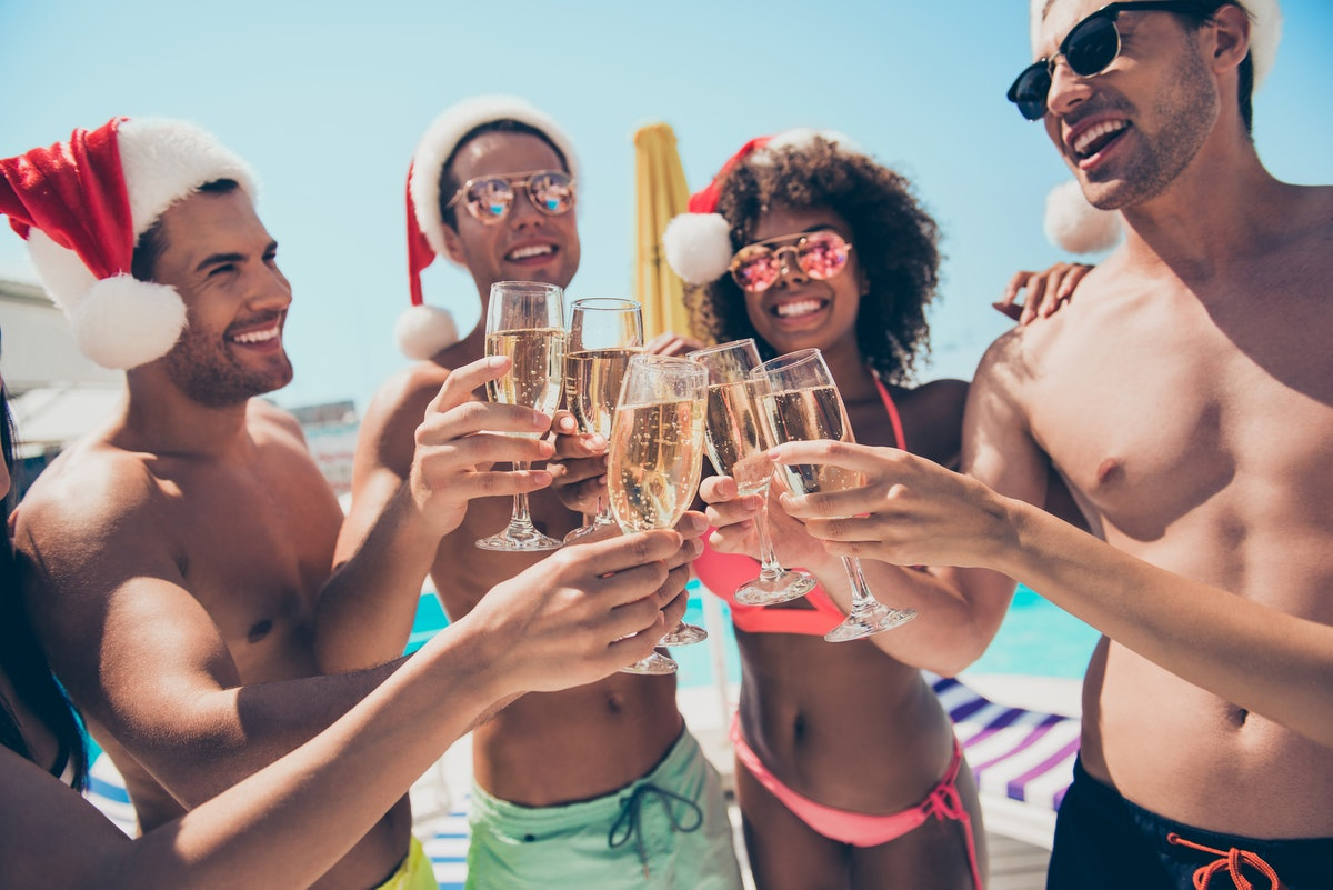 A group of friends dressed in bathing suits and Santa hats smile and toast their champagne flutes on...