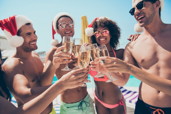 A group of friends dressed in bathing suits and Santa hats smile and toast their champagne flutes on a tropical Christmas vacation.