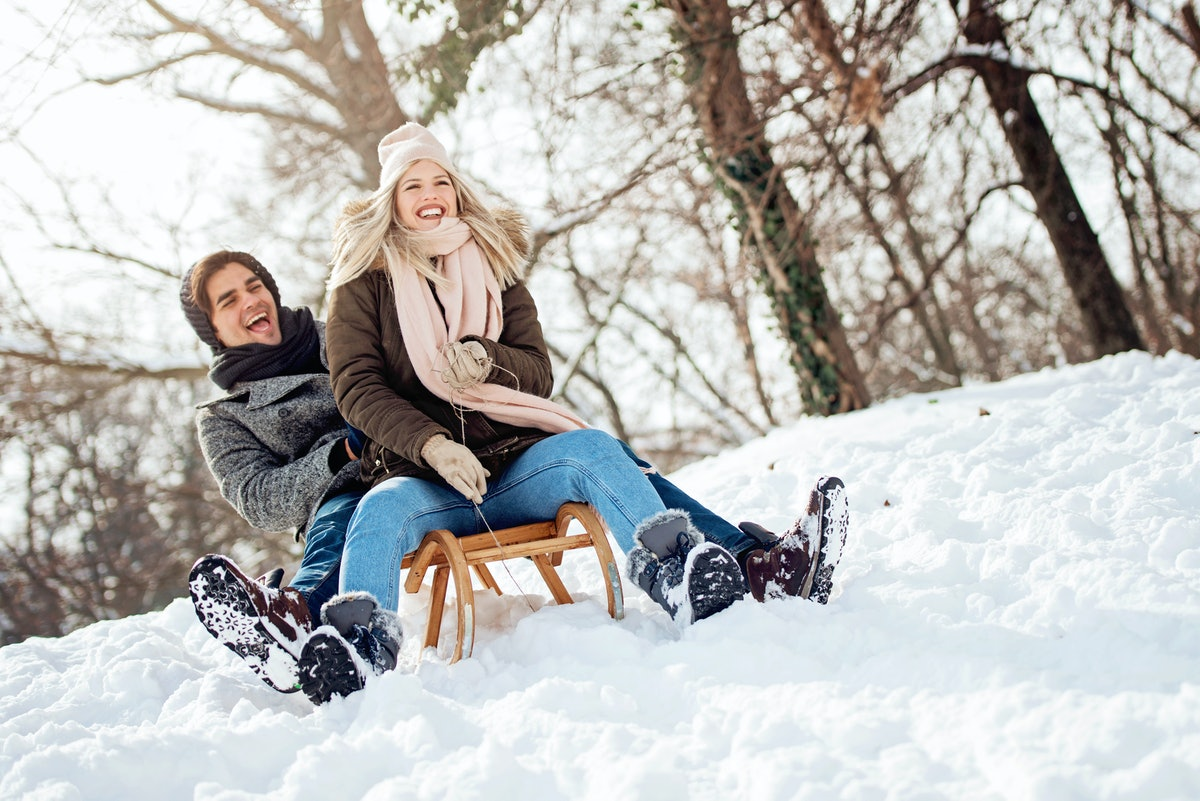 Snow puns, man & woman laughing in snow on sled