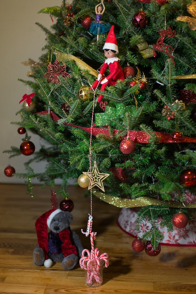 Elf on the shelf sitting on the tree with a bear. Candy cane under the tree. Bear in Christmas hat