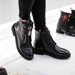 Young fashion woman in black stylish jeans in fashionable leather  boots stands on the white tile in the store. Trendy collection of women's autumn shoes. Close-up of female legs in footwear.
