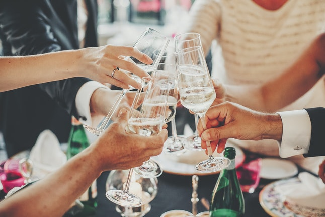 Hands toasting with champagne glasses at wedding reception outdoors in the evening. Family and friends clinking glasses and cheering with alcohol at delicious feast celebration. Christmas party