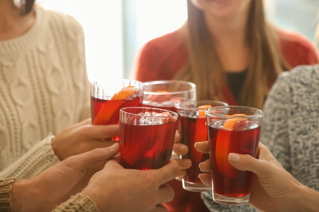 Friends drinking delicious mulled wine at party