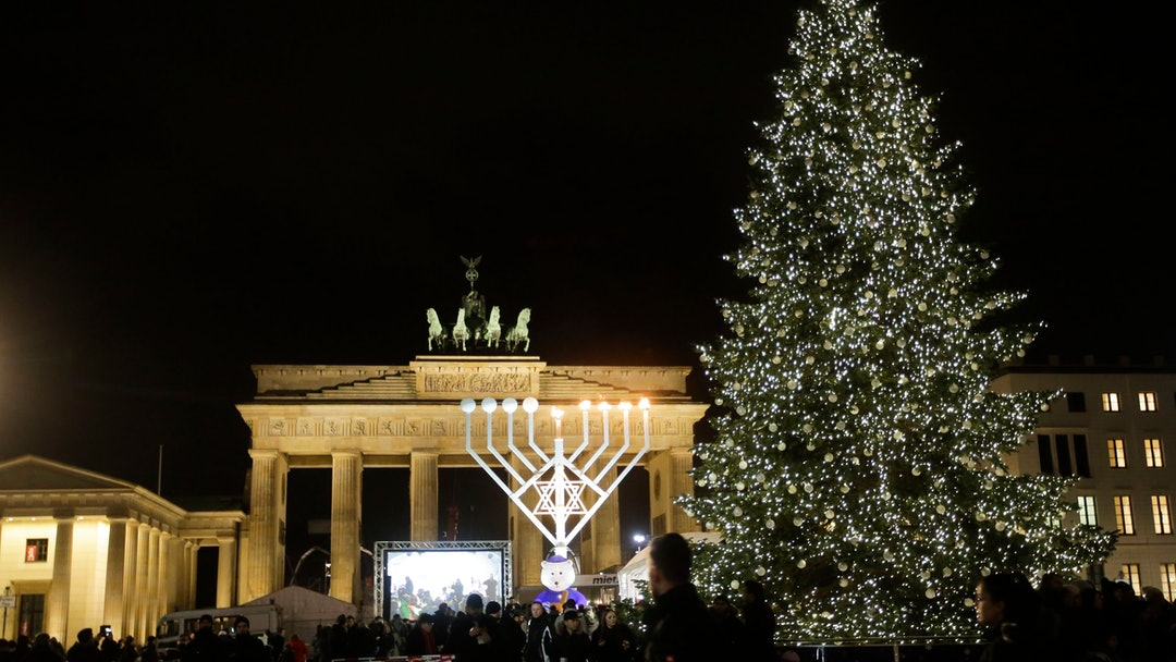 A giant Hanukkah Menorah, center, set up by the Jewish Chabad Educational Center, is illuminated at the Pariser Platz in front of the Brandenburg Gate in Berlin, . An Israeli man whose mother was killed in the attack on a Berlin Christmas market lit a candle on a 10-meter (33-foot) menorah at the city's Brandenburg Gate. Elyakim's mother, Dalia, was one of 12 people killed when a hijacked truck officials said was driven by Tunisian Anis Amri plowed into the market Dec. 19