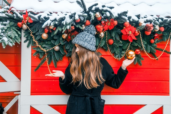 A woman in winter clothes poses with Christmas decorations in a holiday-named town.