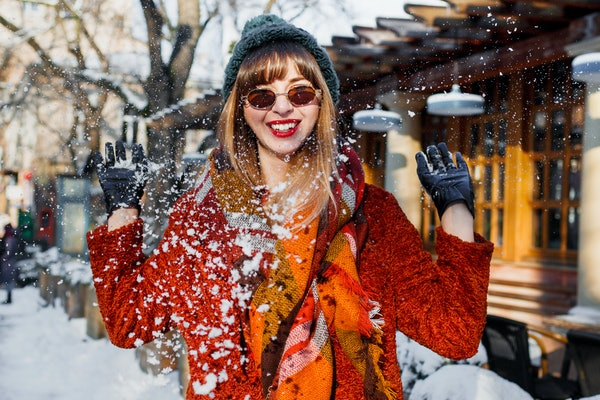 A woman in colorful winter attire plays with the snow in a quaint city.