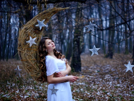 Beautiful young girl with brown curly hair. White dress on the perfect figure of the model. Month, handmade stars made of straw, cardboard, foil. New Year fairy tale, magic motive in the winter forest