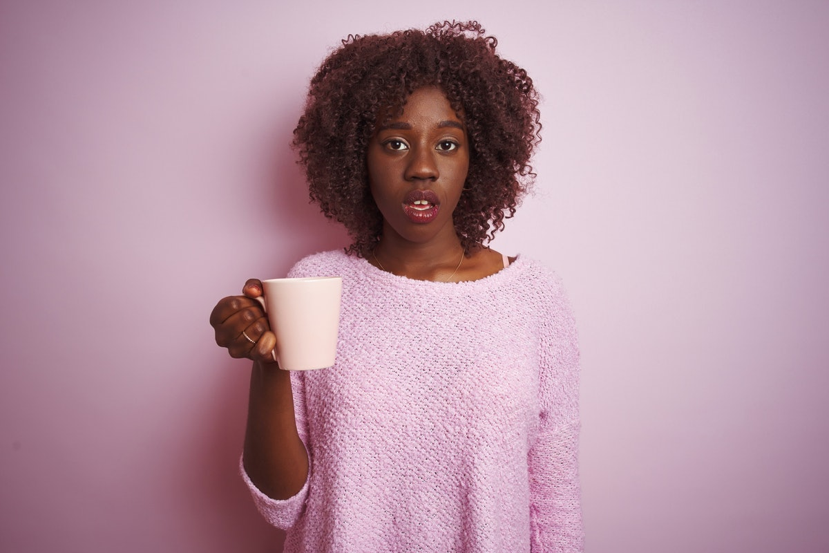 Young african afro woman holding cup of coffee standing over isolated pink background scared in shoc...