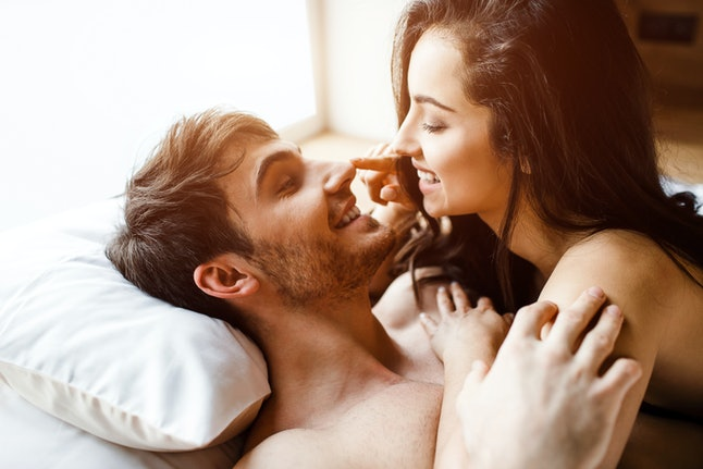 Young sexy couple have intimacy on bed. Cheerful nice positive happy people smile to each other. She lying on him. Happy couple together. Daylight.