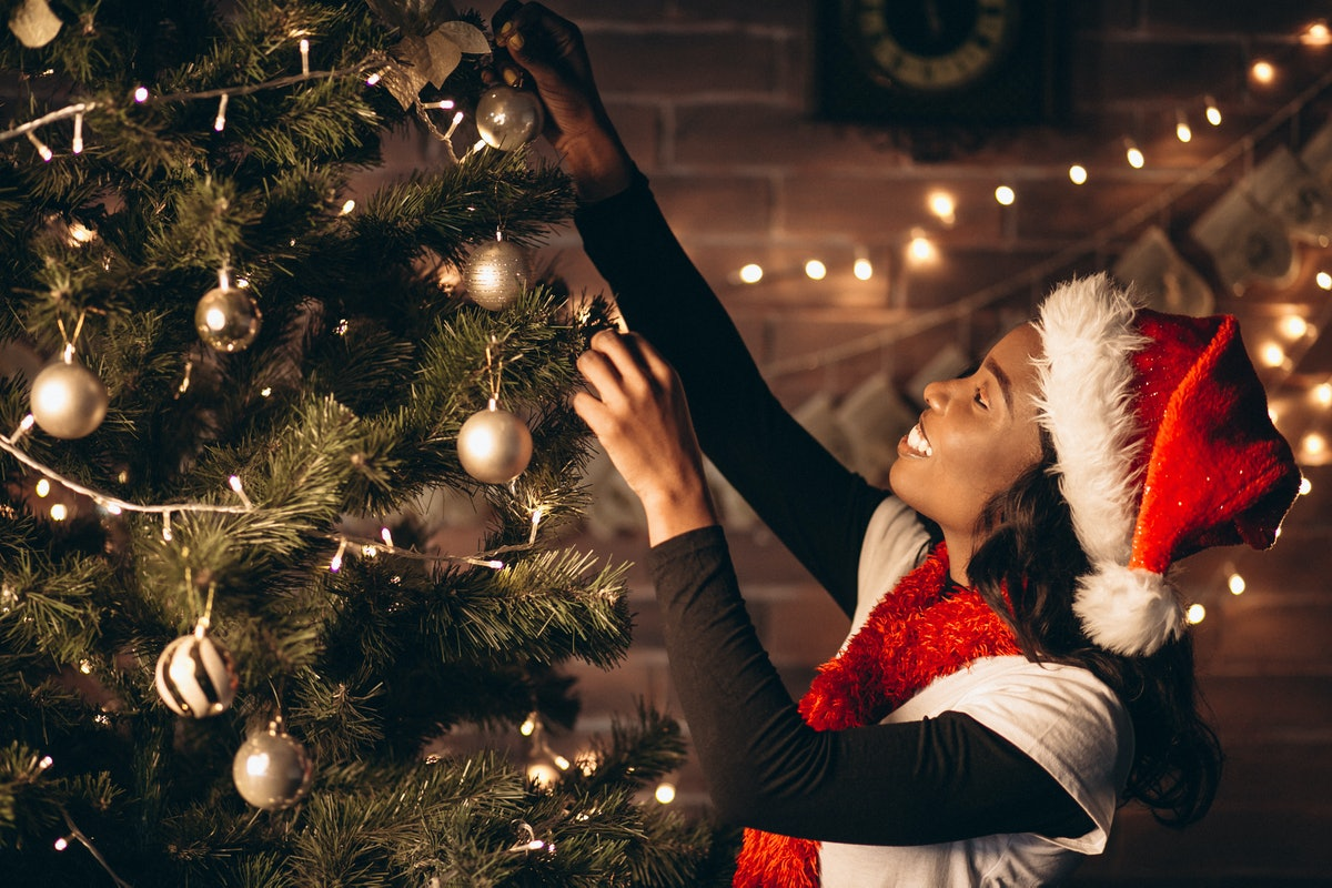 A woman wearing a Santa hat smiles while she decorates her Christmas tree.