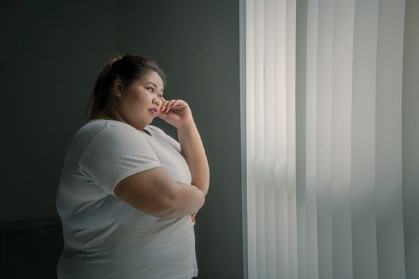Picture of pensive obese woman looking out the window while standing in the dark room