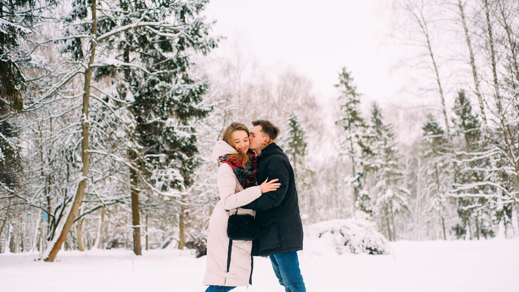 A happy couple hugs in the snow while the guy kisses his girlfriend on the cheek.